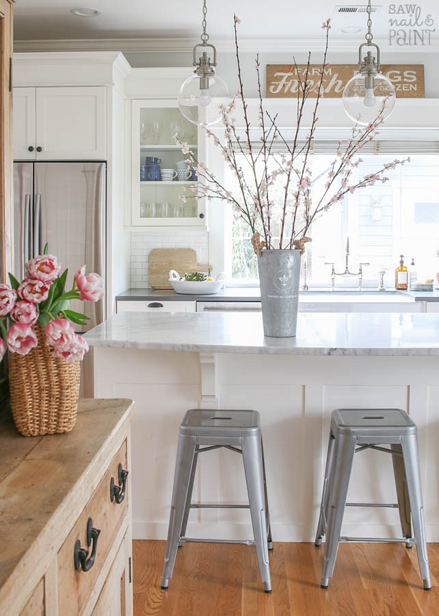 Spring Farmhouse Tours. Cut flowers displayed on an antiwue wood hutch gives the perfect charm to this farmhouse kitchen