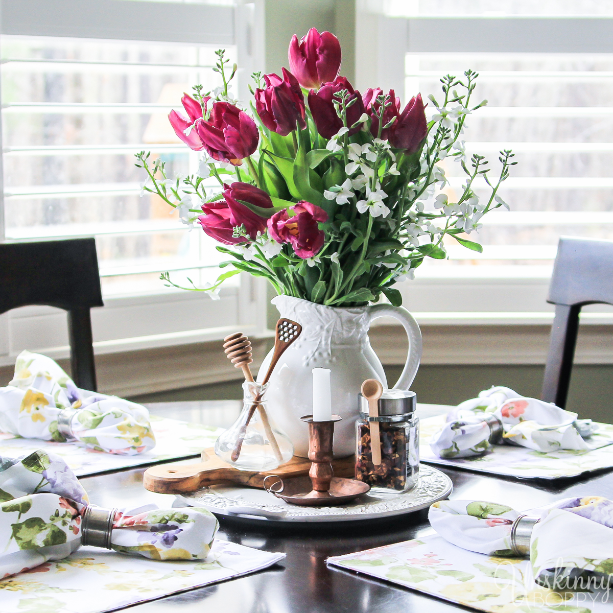 Spring Farmhouse Tours. Find some new floral placemats and napkins to lighten up your dark kitchen table. Add tulips in a carafe for the perfect spring centerpiece.