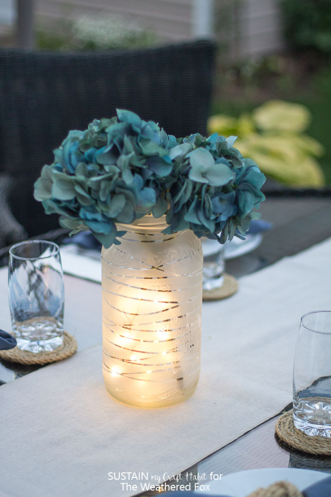 Learn how to upcycle a large glass jar to a gorgeous lantern centerpiece. Beautiful summer patio or wedding decor idea!