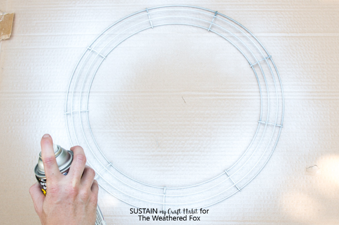 Spray painting a wire wreath frame white