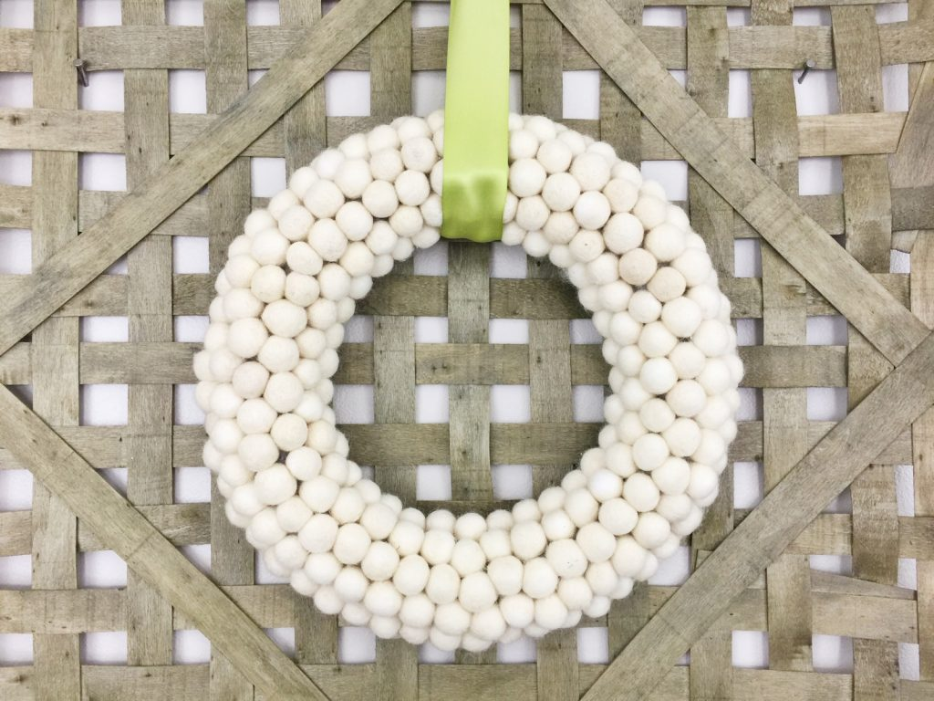 If you're loving pom pom crafts, then you are going to love this white felt ball wreath tutorial! I show you how to make an easy felt pom pom wreath that will look amazing as part of your home decor for any season!