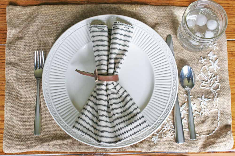 farmhouse table setting, ticking cloth napkin, leather napkin ring, burlap placemat, white plate